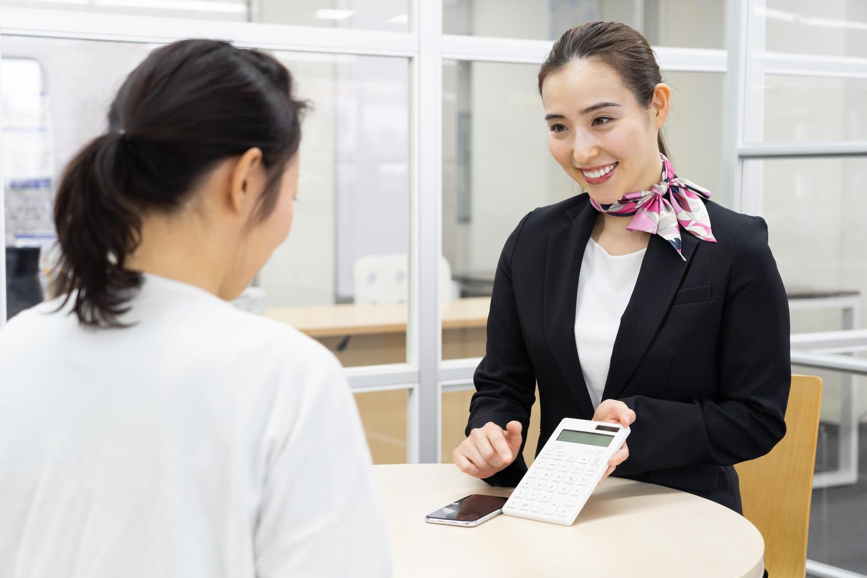 Uma mulher mostrando uma calculadora para outra mulher