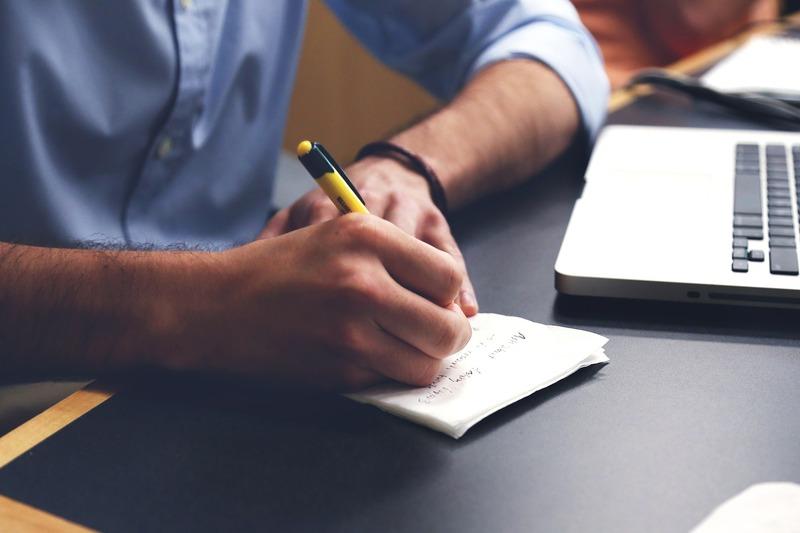 homem escrevendo sobre planejamento de gestão em papel e caneta