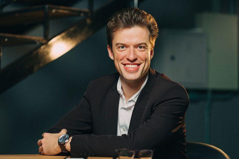 o empresário e professor Arthur Igreja sorri para a câmera com um paletó preto e blusa branca