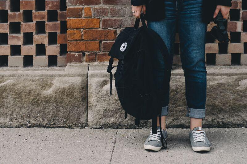 pernas de aluno vestido de calça jeans e segurando mochila cuja ideia é o aluno que se matriculou através de uma promoção de black friday