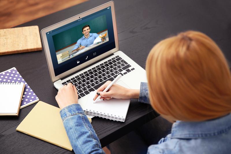 na imagem consta uma aluna estudando na modalidade semipresencial com o notebook em sua frente