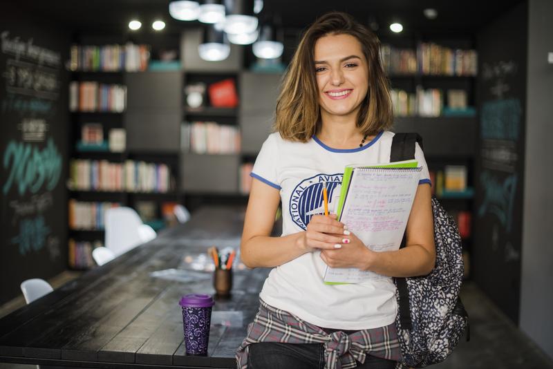 a isenção de taxas pode facilitar a matrícula do aluno na IES. Na imagem, uma possível aluna da universidade sorri.