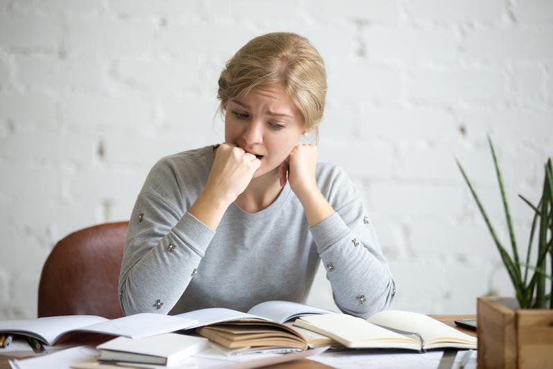aluna aflita com a mão na boca e face pensativa em relação às contas que a família precisa pagar no início de ano. Tudo isso dificulta a matrícula do aluno.
