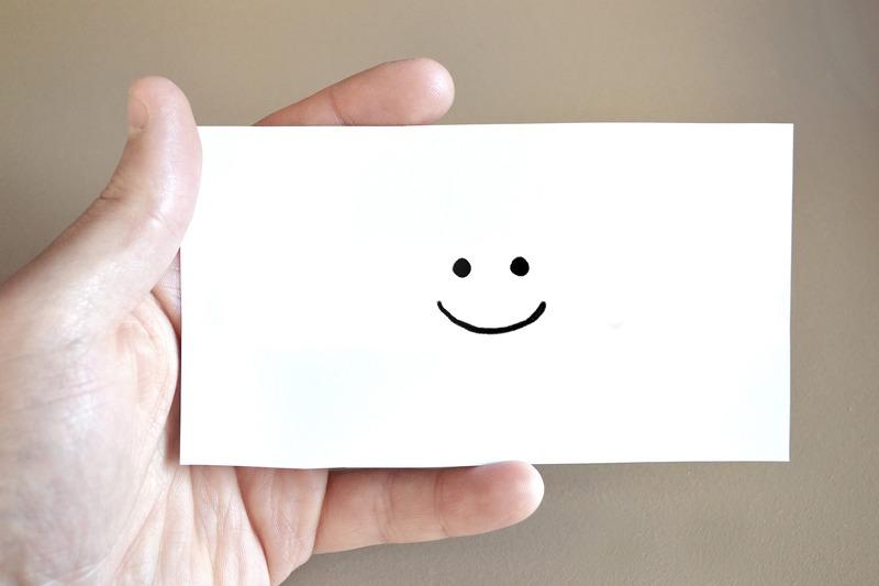uma mão segura um cartão de visitas com o desenho de uma carinha feliz, simbolizando um feedback posisitivo