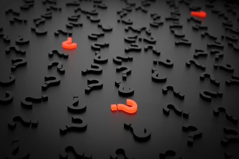 Diversos pontos de interrogação dispersos em um fundo preto, com alguns deles em vermelho, o que simboliza dúvidas.