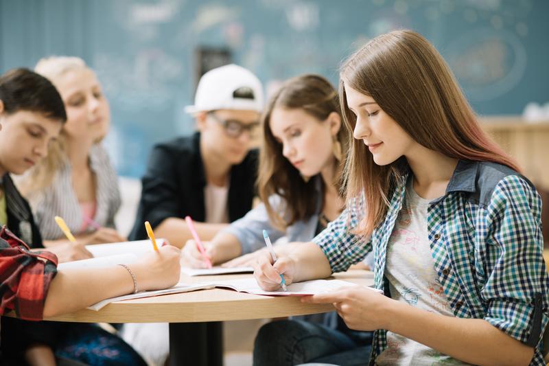 cinco jovens estudantes estudam em uma mesa de uma escola de franquia