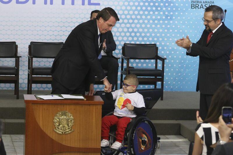 Jair Bolsonarom, ministro e criança em cerimônia de lançamento da nova carteirinha de estudante