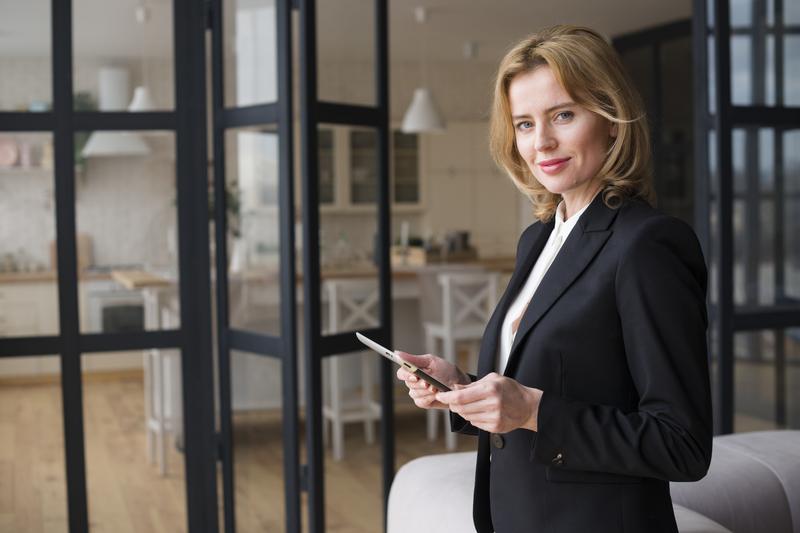 mulher de negócios de terninho preto segurando um tablet