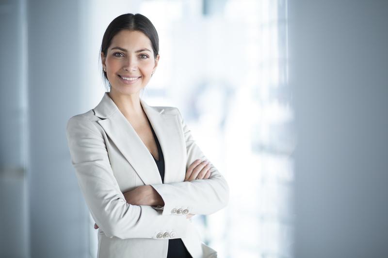 Executiva graduada sorrindo para a câmera de terninho cor clara