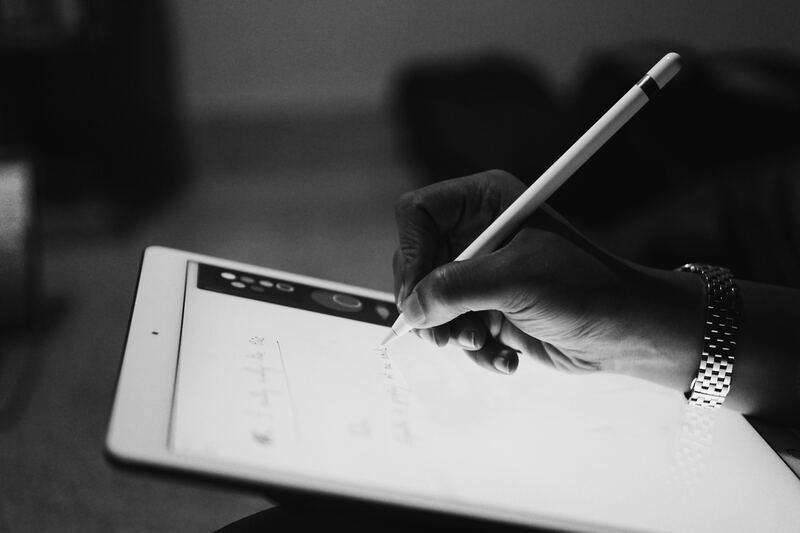 uma mão escreve em um tablet representando uma instituição de ensino inovadora