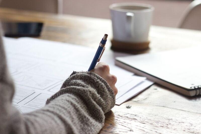 estudante escrevendo em papeis e com uma xícara de chá a frente