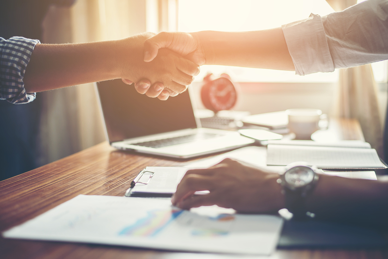 Duas pessoas de negócios dão um aperto de mão celebrando um negócio fechado