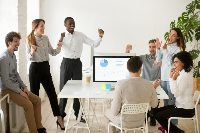 Sete jovens de um grupo diverso de pessoas celebram vitória de negócios a partir de estratégias de marketing