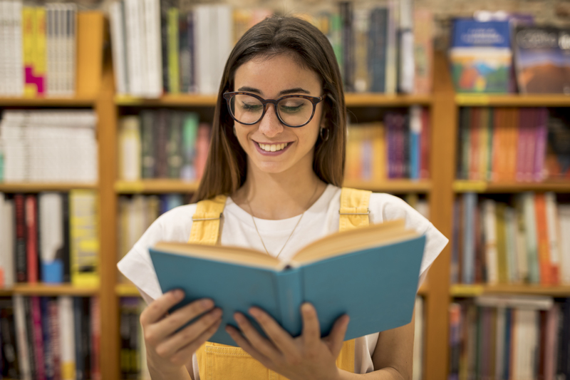 estudante lê livro de costas para uma estante de livros semelhante a de uma biblioteca e sorri