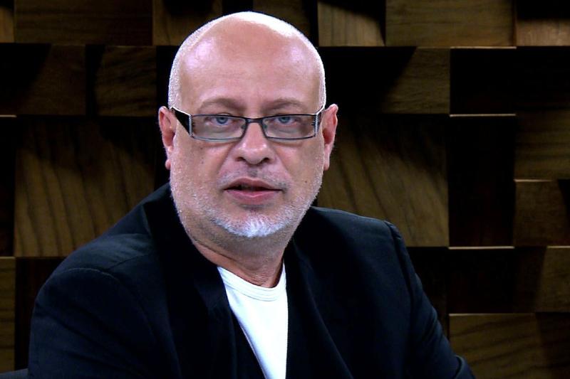 Luiz Felipe Pondé de óculos olhan do para a câmera com paletó preto e camisa branca