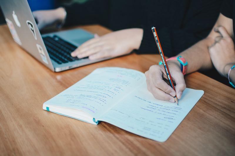 duas pessoas estão estudando e enquanto uma está operando o notebook, a outra está escrevendo em um caderno de anotações. A imagem simboliza provas analógicas e digitais.