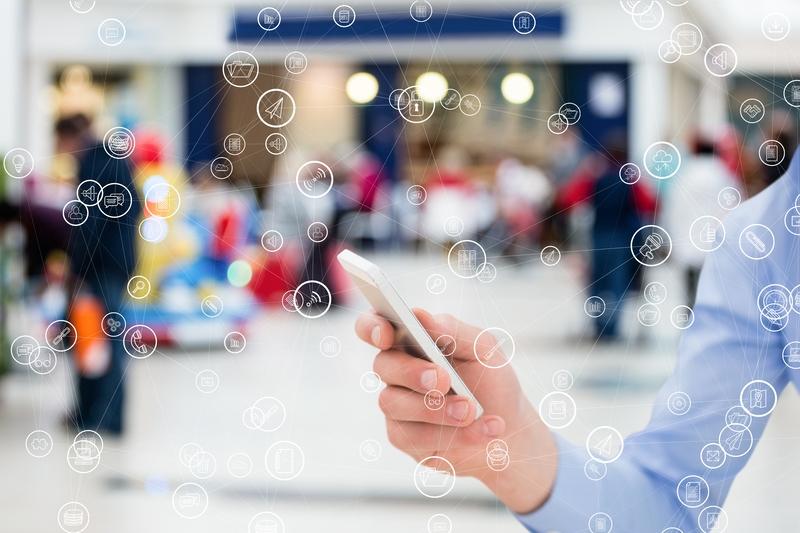 A mão de um homem segura o celular e simboliza a segurança de processos online