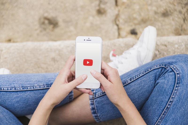 usuária da rede social youtube com o celular na mão interagindo