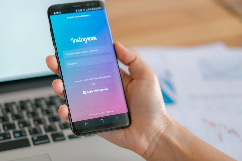 Usuário da rede social instagram com o celular na mão