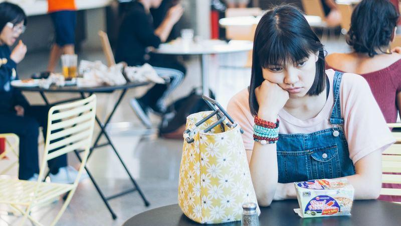 estudante asiática triste sentada em refeitório, público-alvo da campanha setembro amarelo