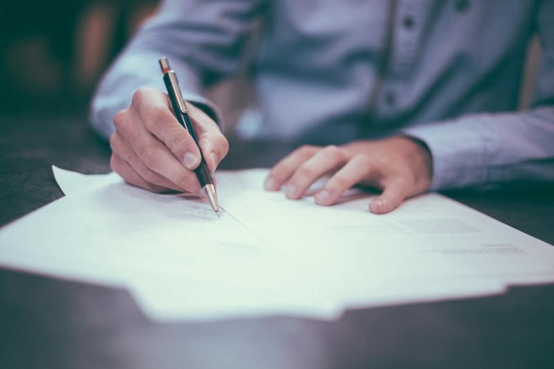 mãos masculinas escrevem em papel com caneta. Imagem reflete a empregabilidade