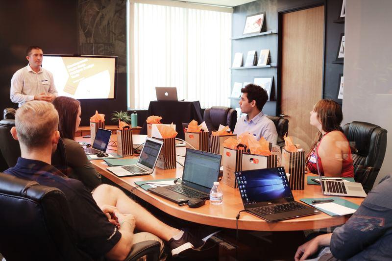 reunião de marketing com profissionais diversos em uma grande mesa com seus notebooks. Parcerias entre empresas e instituições de ensino proporcionam ambientes como esse