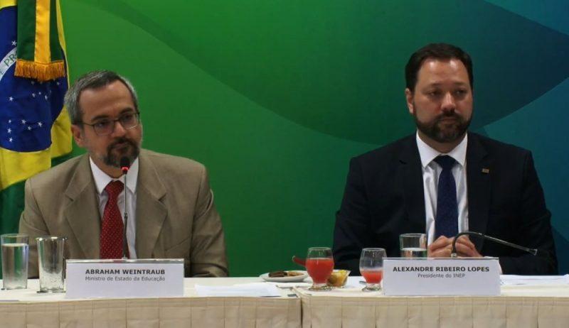 Dois homens sentados, ao lado da bandeira do Brasil. O Ministro da educação do Brasil e presidente do Inep sentados numa mesa para coletiva de imprensa.